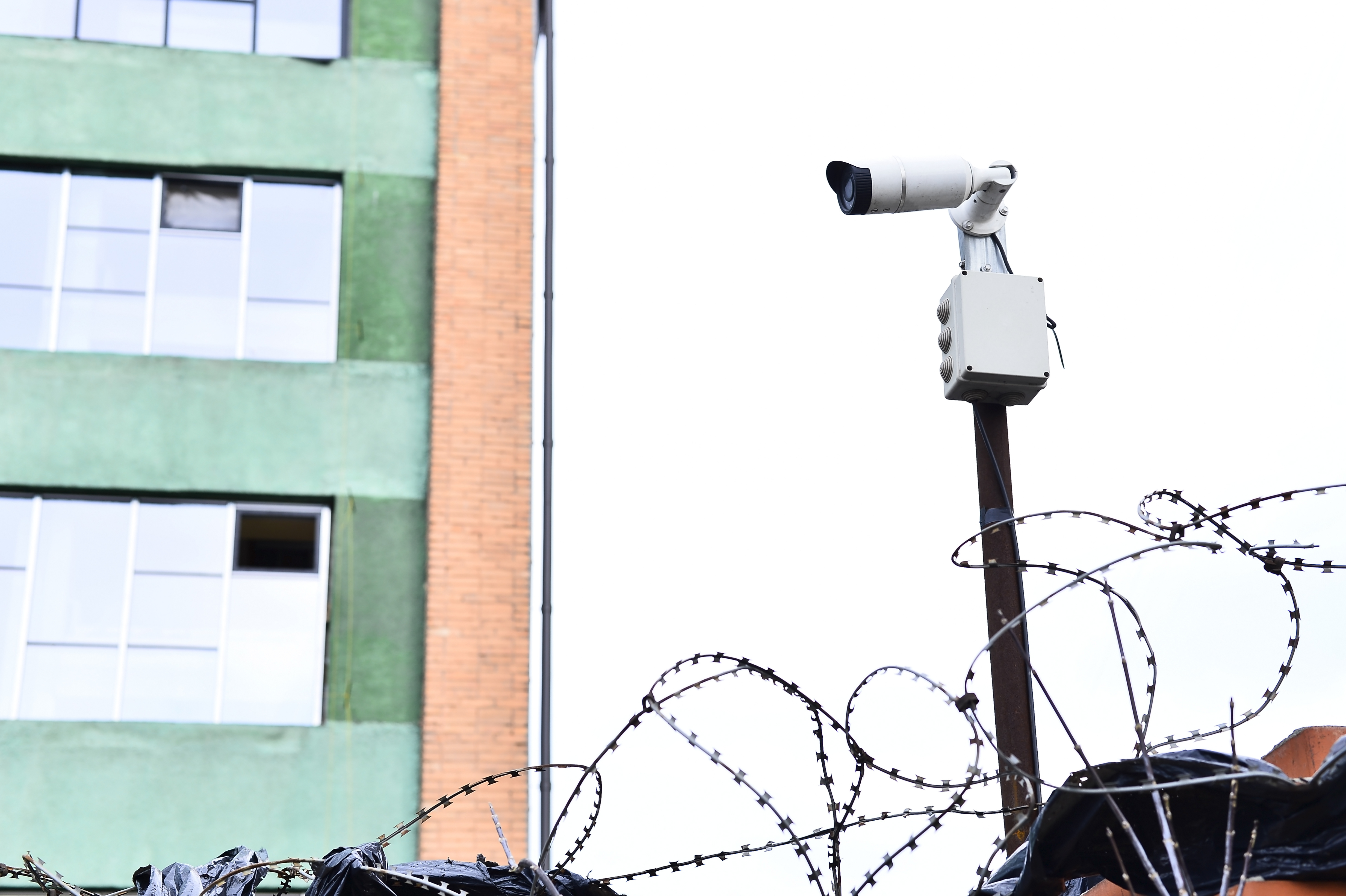 Camera video surveillance on the building background mounted on a brick wall, fenced with barbed wire.